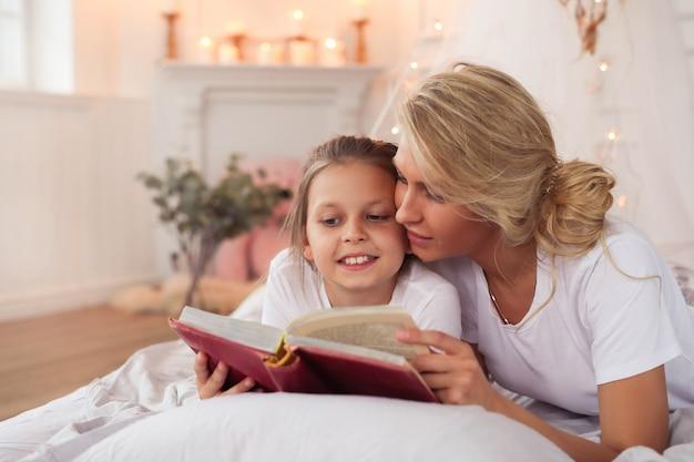 Familie scène. gelukkige moeder en dochter in een bed