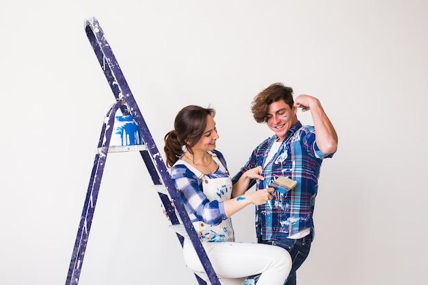 Familie schilderen muur, lachen en zien er erg blij uit.