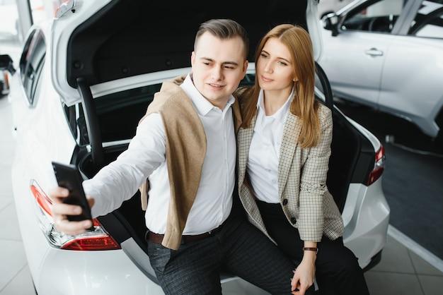 Familie selfie in dealer. gelukkig jong koppel kiest en koopt een nieuwe auto voor het gezin.