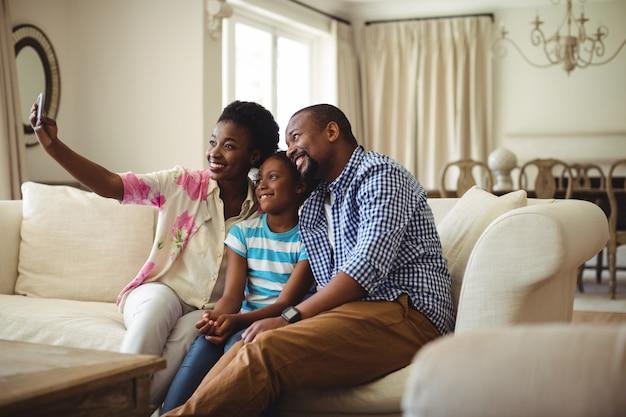 Familie selfie te nemen op de mobiele telefoon in de woonkamer