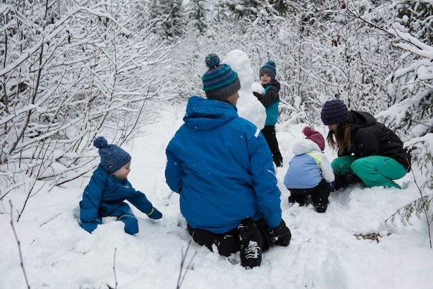 Familie sneeuwpop maken op besneeuwde dag