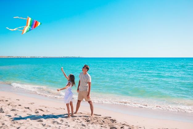 Familie spelen met een vlieger op het strand