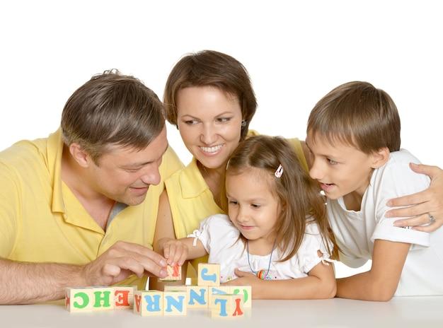 Familie spelen met kubussen geïsoleerd op wit