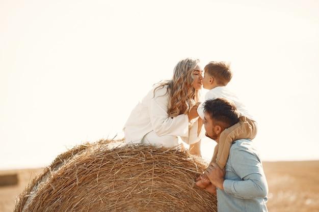 Familie spelen met zoontje in een tarweveld op zonsondergang. het concept van zomervakantie. familie tijd samen doorbrengen op de natuur.