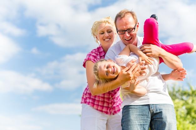 Familie stoeien op veld met ouders die kind dragen