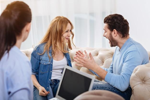 Familie strijd. woedende knappe bebaarde man die naar zijn vrouw kijkt en tegen haar schreeuwt terwijl hij in het kantoor van de psycholoog zit