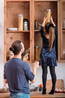 Familie teamwerk. meisje dat haar vader helpt om kruik met spaghetti op keukenplank te bereiken.