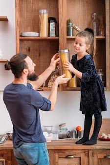 Familie teamwerk. vader koken in de keuken met schattige kleine assistent. jonge dochter die kruik met spaghetti van plank helpt te krijgen.