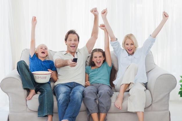 Familie televisie kijken en armen heffen