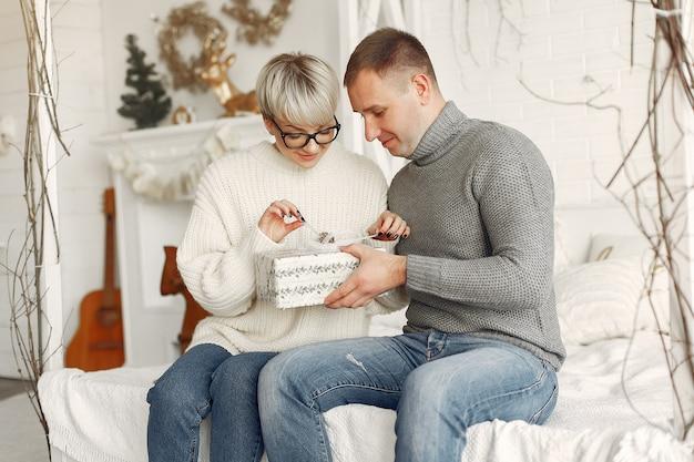 Familie thuis. echtpaar in de buurt van kerstversiering. vrouw in een grijze trui.