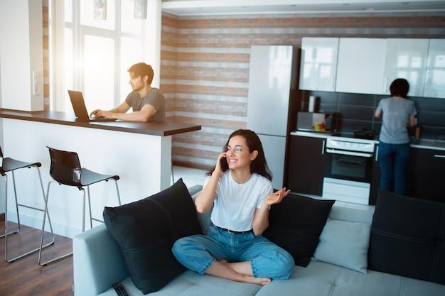 Familie thuis. iedereen heeft het druk met zijn eigen bedrijf. een jonge vrouw praat aan de telefoon. een man gebruikt een laptop terwijl een volwassen vrouw in de keuken kookt