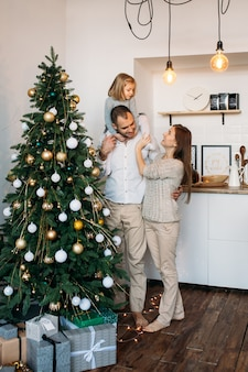 Familie thuis in de buurt van de kerstboom en kerstcadeautjes. vrolijk kerstfeest en een gelukkig nieuwjaar!