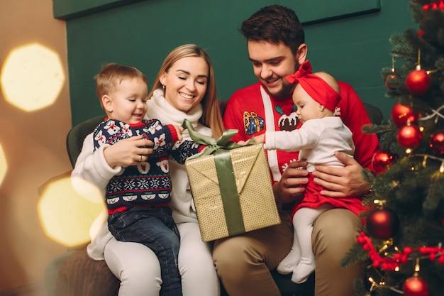 Familie thuis in de buurt van de kerstboom