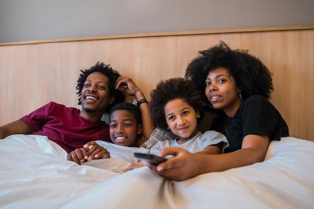 Familie thuis kijken naar een film op bed.
