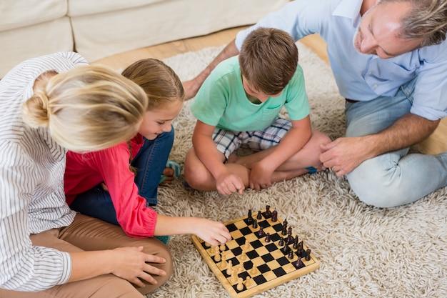 Familie thuis schaken samen in de woonkamer