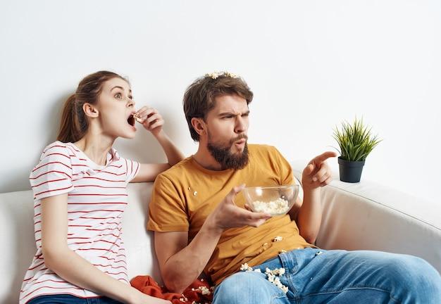 Familie thuis zittend op de bank met popcorn films kijken leuk
