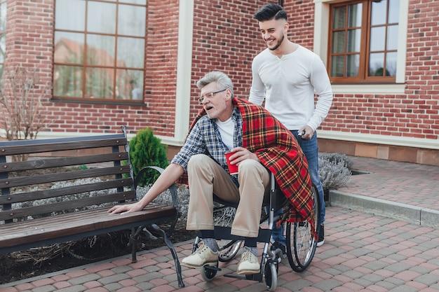 Familie tijd. de zoon die zijn oudere vader op rolstoel in verzorgingstuin helpt.
