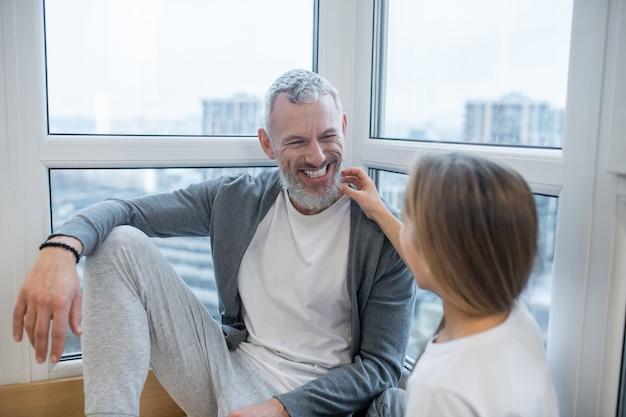 Familie tijd. een vader die met zijn dochter voor het raam zit
