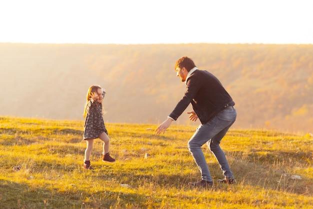 Familie tijd. foto van schattig klein meisje loopt in papa richting om haar te vangen