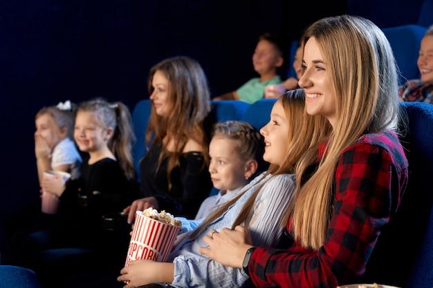 Familie tijd samen doorbrengen in de bioscoop. selectieve aandacht van jonge moeder die dochtertje op knieën houdt en lacht tijdens het kijken naar film en het eten van popcorn
