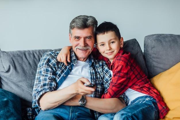 Familie tijd. vrolijke kleinzoon knuffelen met zijn grootvader. woonkamer.