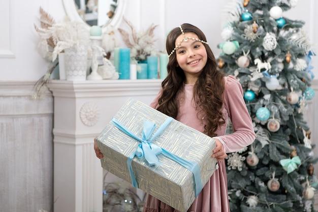 Familie tradities. kerstcadeau. klein meisje ontving vakantiegift. beste kerstcadeaus. kind enthousiast over haar geschenk. kid klein meisje in elegante jurk en geschenkdoos kerstboom achtergrond.
