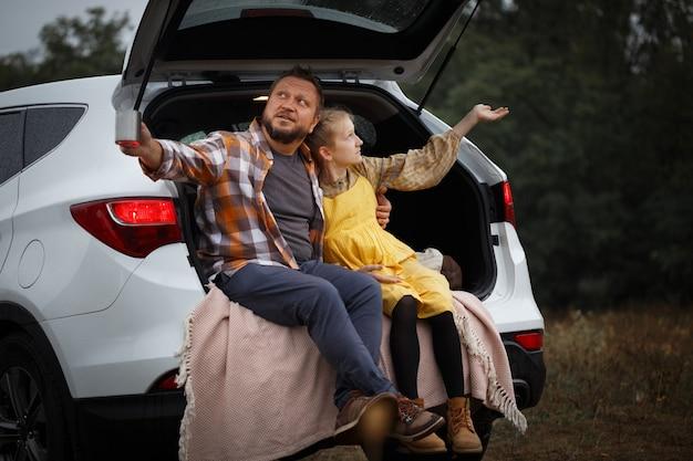 Familie uitje. met de auto reizen. vader met dochter zit in de koffer en drinkt thee