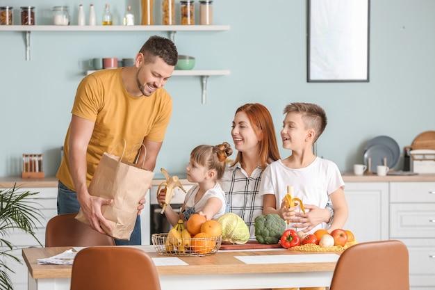 Familie uitpakken van verse producten uit de markt in de keuken