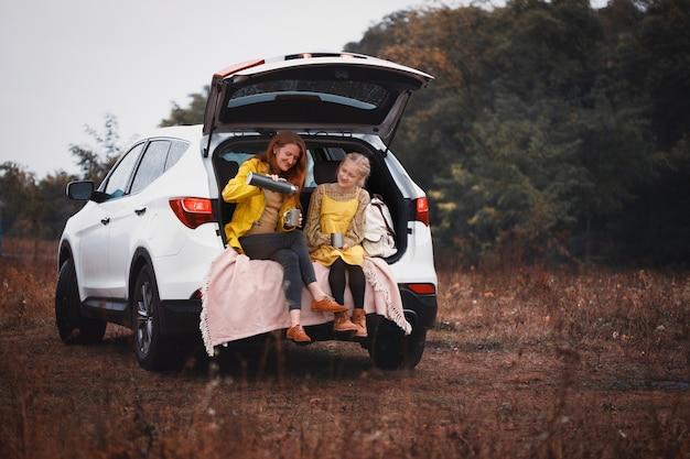 Familie-uitstapje - gelukkige meisjes reizen met de auto. mama met dochter zit in de koffer en drinkt thee