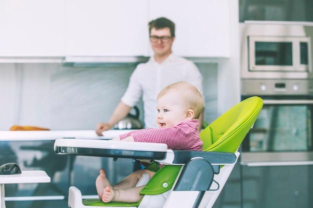 Familie vader baby voeden in de keuken gelukkig samen thuis lachend in de keuken