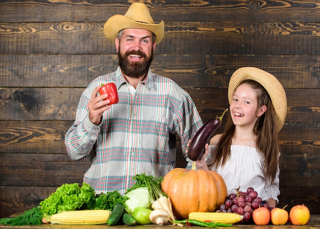 Familie vader boer tuinman met dochter in de buurt van oogstgroenten. boerderijmarkt met herfstoogst. familie boerderij festival concept. platteland familie levensstijl. man bebaarde rustieke boer met kind.