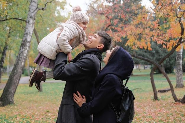 Familie vader en moeder op een wandeling in het park spelen met dochter.
