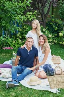Familie vader, moeder en dochter in de tuin in de zomer op een picknickrust