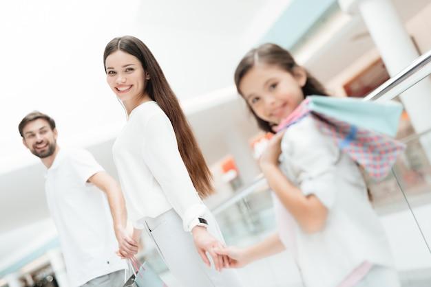 Familie, vader, moeder en dochter met boodschappentassen.