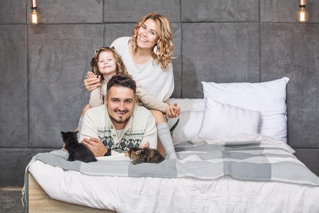 Familie vader moeder en lieve dochter blij samen met kleine pluizige kittens op het bed