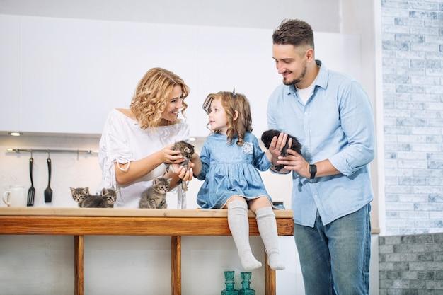 Familie vader, moeder en lieve dochter gelukkig samen met kleine pluizige kittens in de keuken in een licht interieur