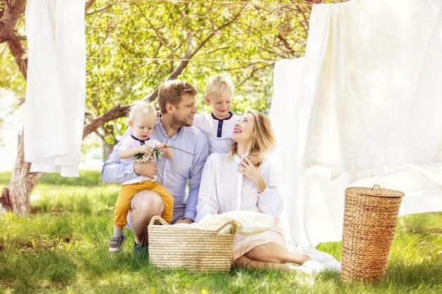Familie vader moeder en twee zonen mooi en gelukkig samen hangen schone was in de tuin