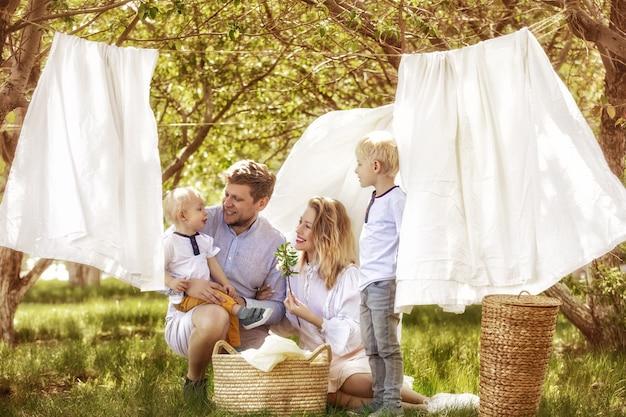 Familie vader, moeder en twee zonen, mooi en gelukkig samen hangen schoon wasgoed in de tuin
