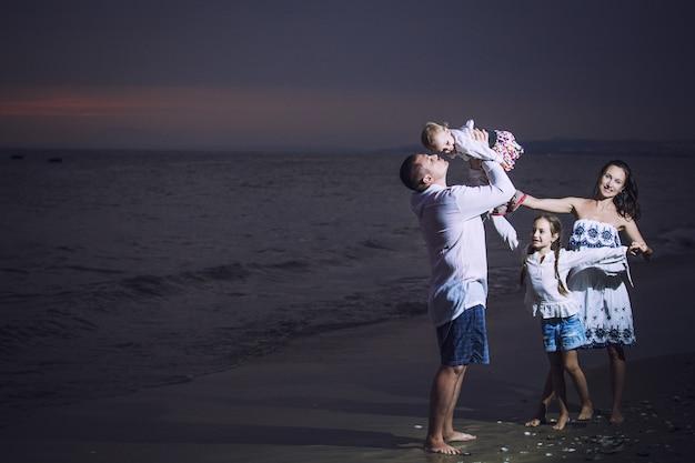 Familie vader moeder kind meisje en baby op het strand tegen de zee en de prachtige zonsondergang