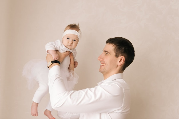Familie, vaderschap en mensen concept-happyfather met kleine baby dochter op een lichte achtergrond holding