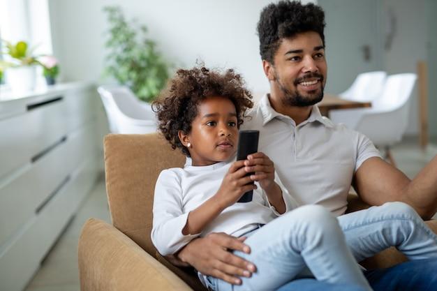 Familie, vaderschap liefde mensen concept. gelukkige vader en dochter die thuis tv kijken