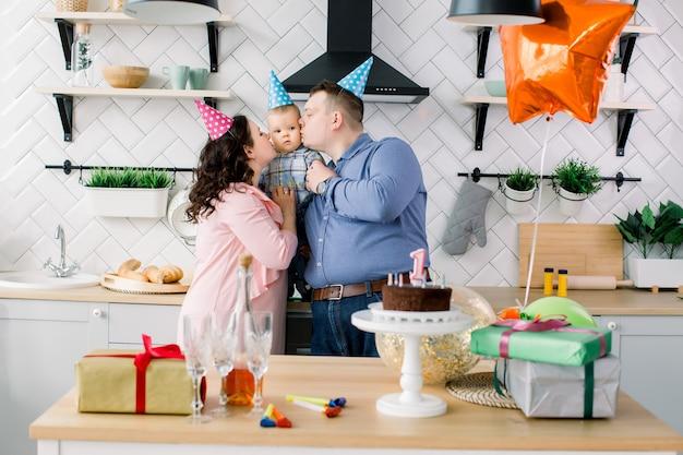 Familie, vakantie en mensenconcept - moeder, vader en gelukkig weinig zoon thuis verjaardagsfeestje, ouders kussen babyjongen