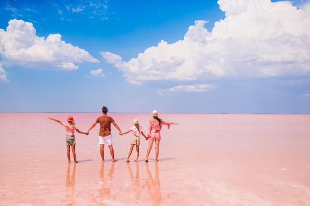 Familie vakantie. gelukkige ouders met twee kinderen op een roze zoutmeer. prachtige natuur en geweldig landschap