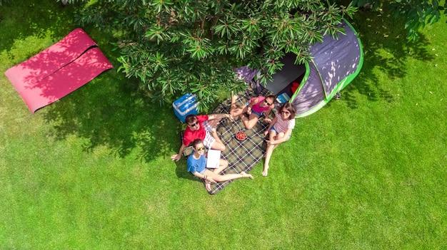 Familie vakantie in camping luchtfoto bovenaanzicht van bovenaf, ouders en kinderen ontspannen en veel plezier in park, tent en kampeeruitrusting onder boom, familie in kamp buiten concept