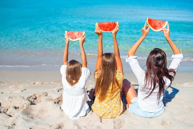 Familie vakantie. moeder en kleine meisjes op vakantie op het strand met plakjes watermeloen