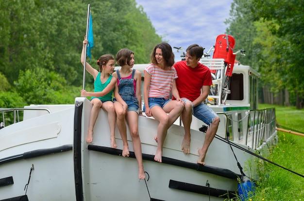 Familie vakantie, reizen op binnenschip in kanaal, gelukkige ouders met kinderen plezier op riviercruise in woonboot