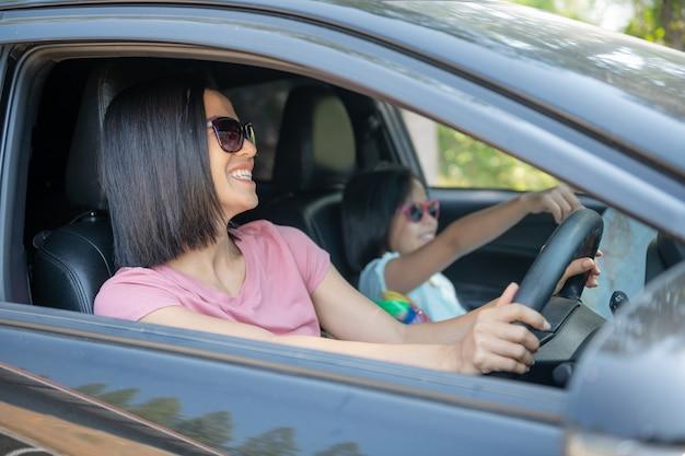 Familie vakantie vakantie, gelukkige familie op een road trip in hun auto, moeder auto rijden terwijl haar dochter naast zit, moeder en dochter reizen. zomerrit met de auto.