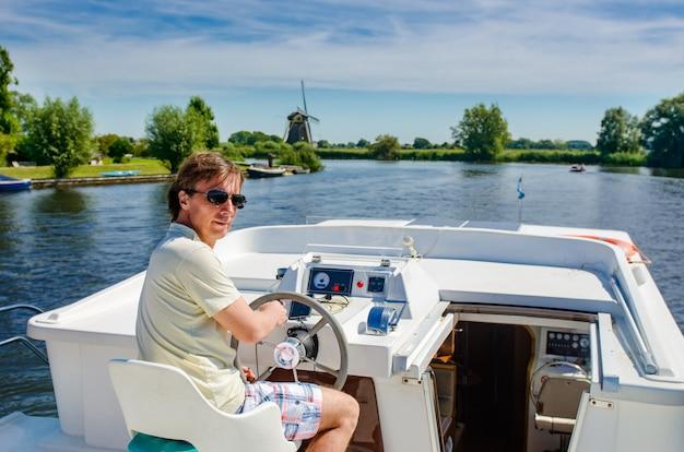 Familie vakantie, zomervakantie reizen op binnenschip in kanaal, man door stuur op riviercruise reis in woonboot in nederland