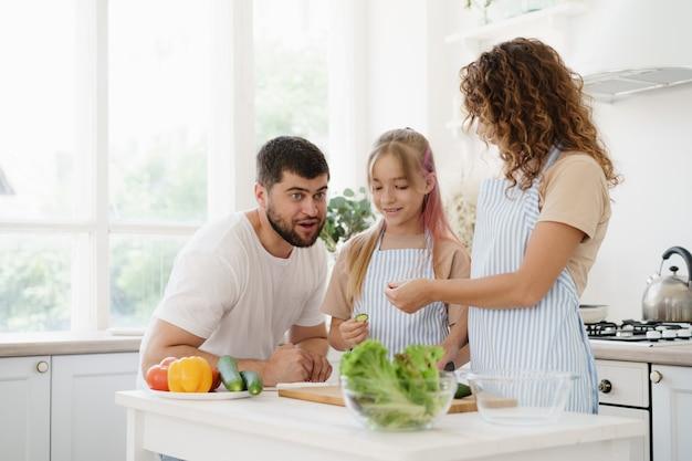 Familie van drie die in de keuken staat en samen een maaltijd kookt