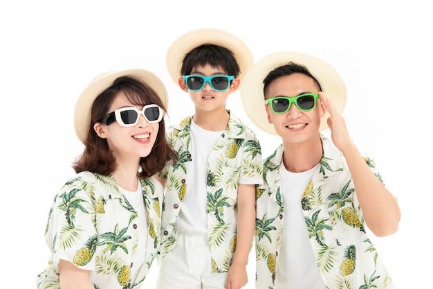 Familie van drie die in zonnebril en strohoeden reizen